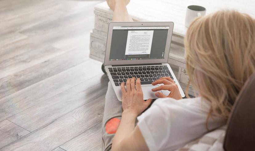 zdjęcie przedstawiające kobietę przygotowującą na komputerze list motywacyjny